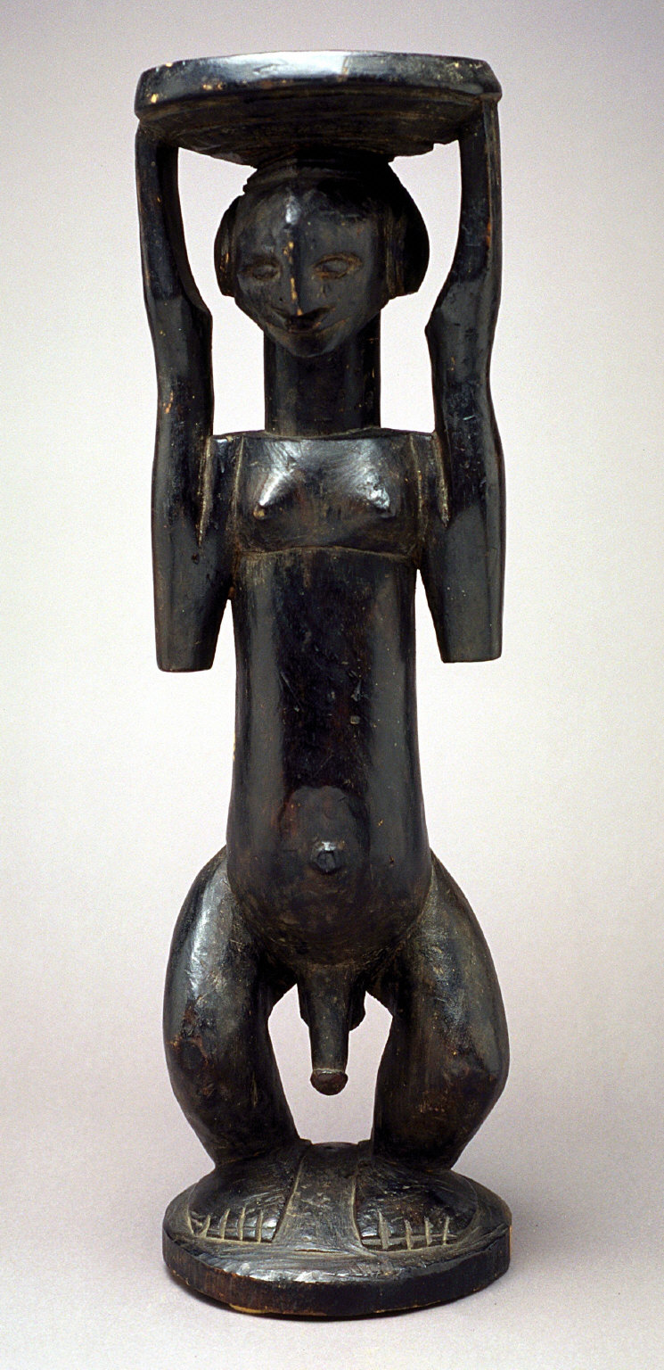 Standing male caryatid with stool schematized arms, extended hands supporting stool, darkly painted wood