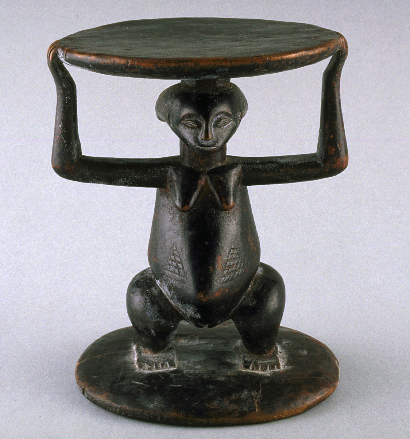 Stool with squatting female holding seat