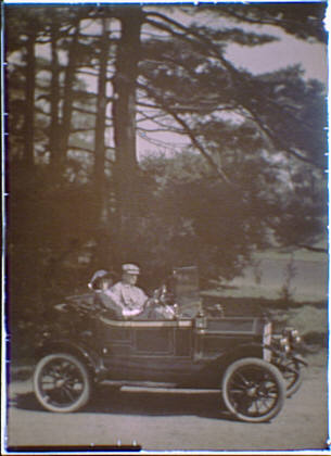 Couple seated in a car parked under large pine trees