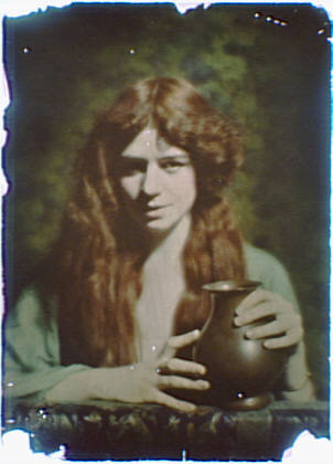 Woman with long red hair holding a vase