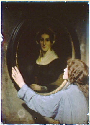 Woman with red hair wearing a blue robe or gown looking at a portrait painting of a woman