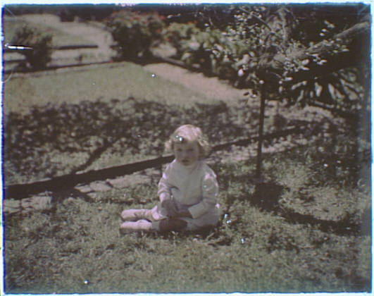 Young child dressed in white seated on grass