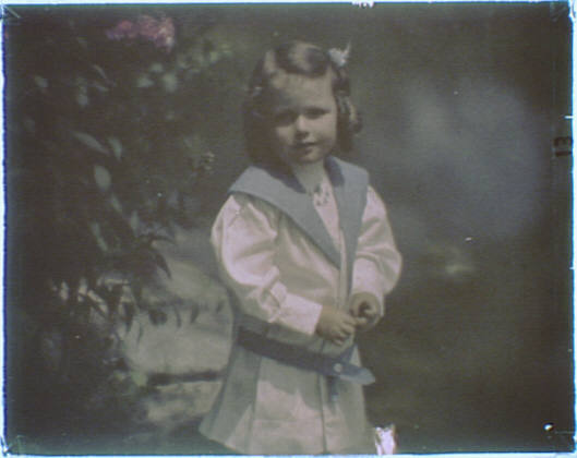 Young girl wearing a white and blue outfit standing outside