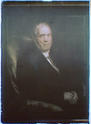 Photograph of a painting of a man with folded hands seated in a chair