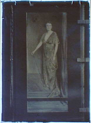 Photograph of a painting of a woman standing and holding a walking stick or a cane