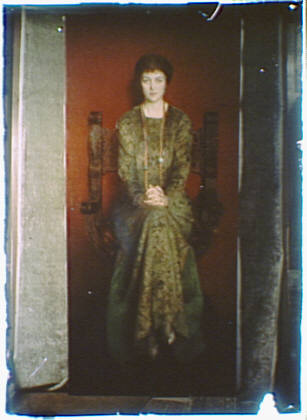 Photograph of a painting of a woman wearing a long dress seated in a chair with her hands folded